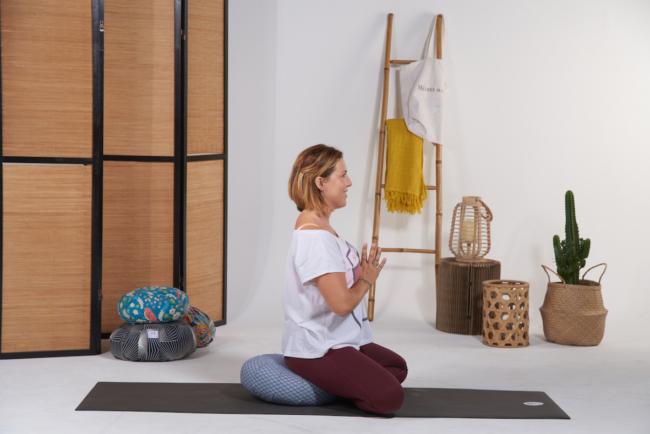 Personne assise en tailleur ou lotus sur le coussin de meditation zafu